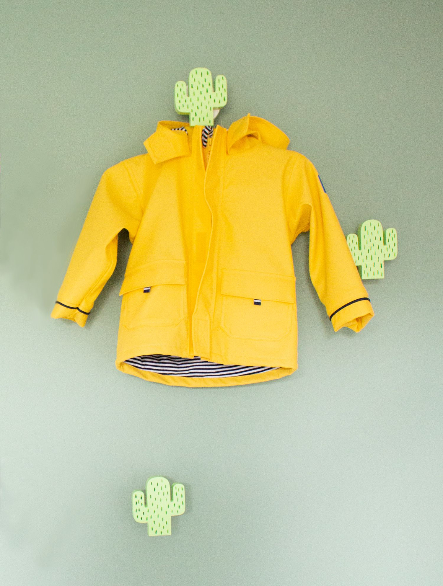 A close up of a child's coat hanging on a cactus shaped hook.