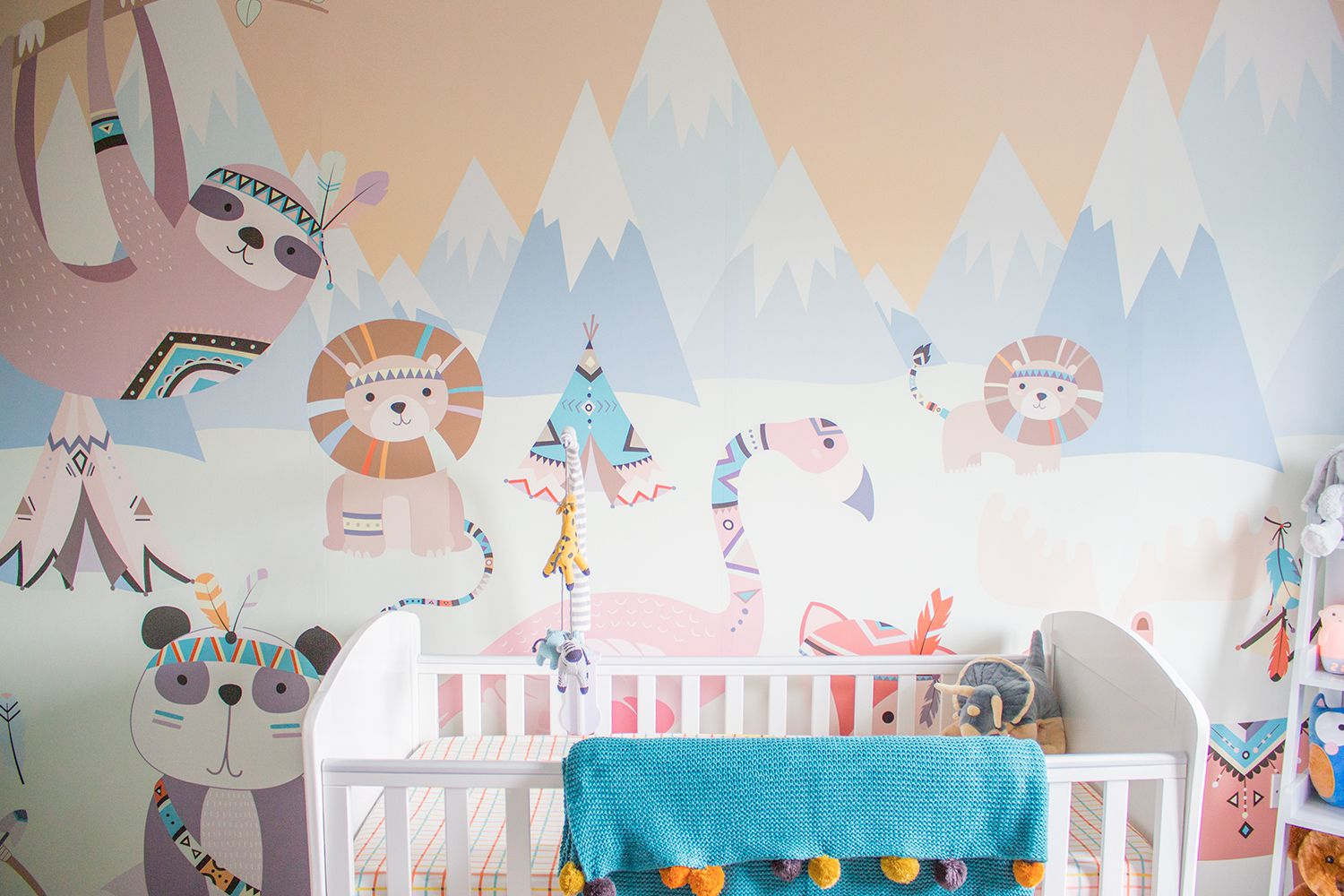 A view of the animal themed wallpaper mural with the white cot in front and colourful blanket draped over the side.