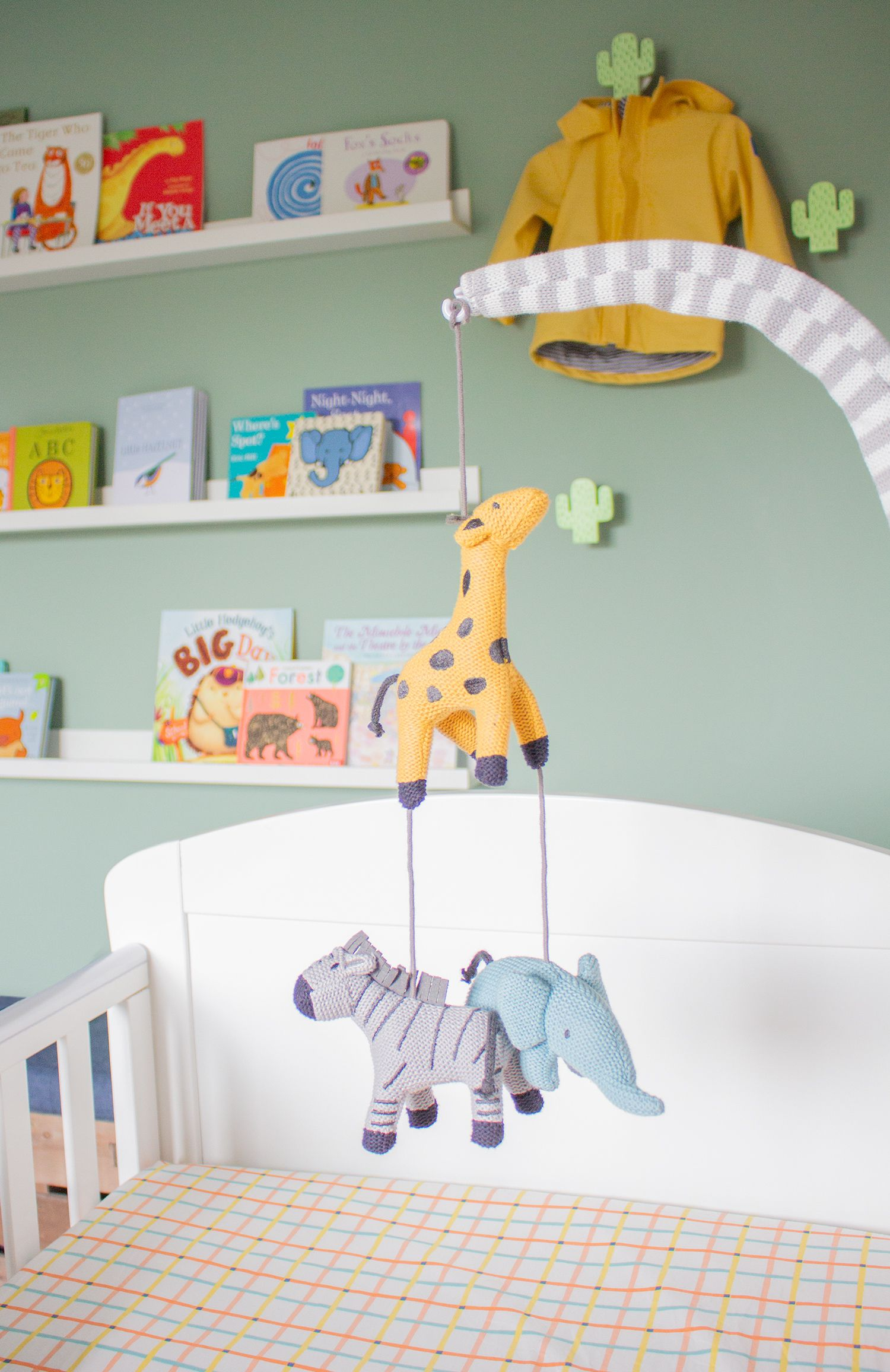 A close up of the soft toy cot mobile which has a giraffe, an elephant and a zebra.