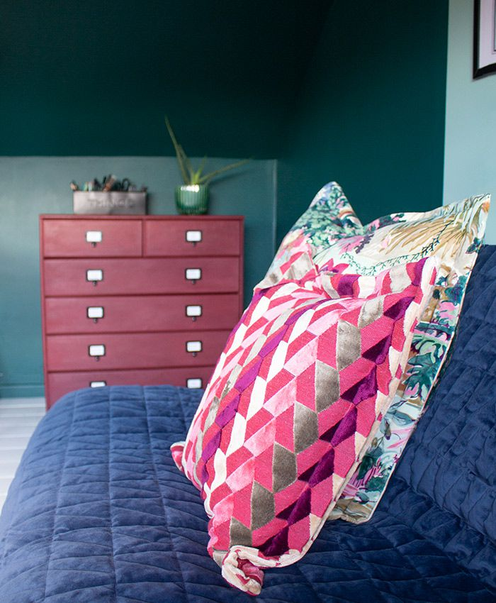 A photo of the patterned cushions on the sofa with the painted chest of drawers in the background.