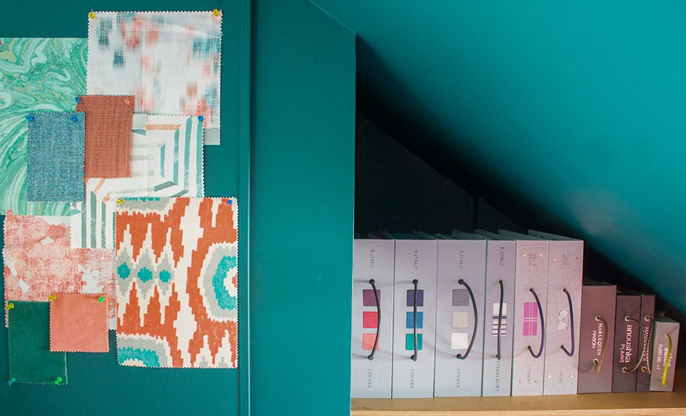 A close up of the plywood shelving holding fabric books, and the painted noticeboard.