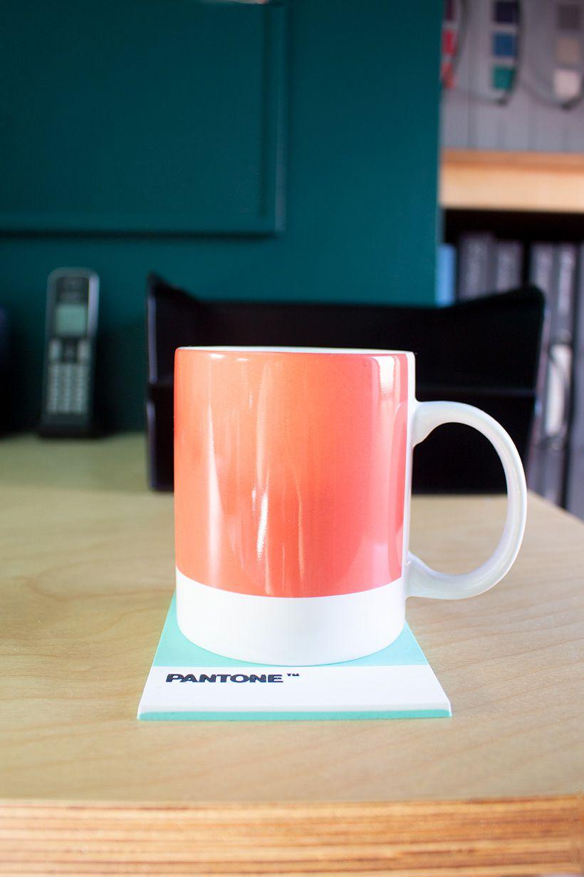 A close up of an orange mug on the desk.