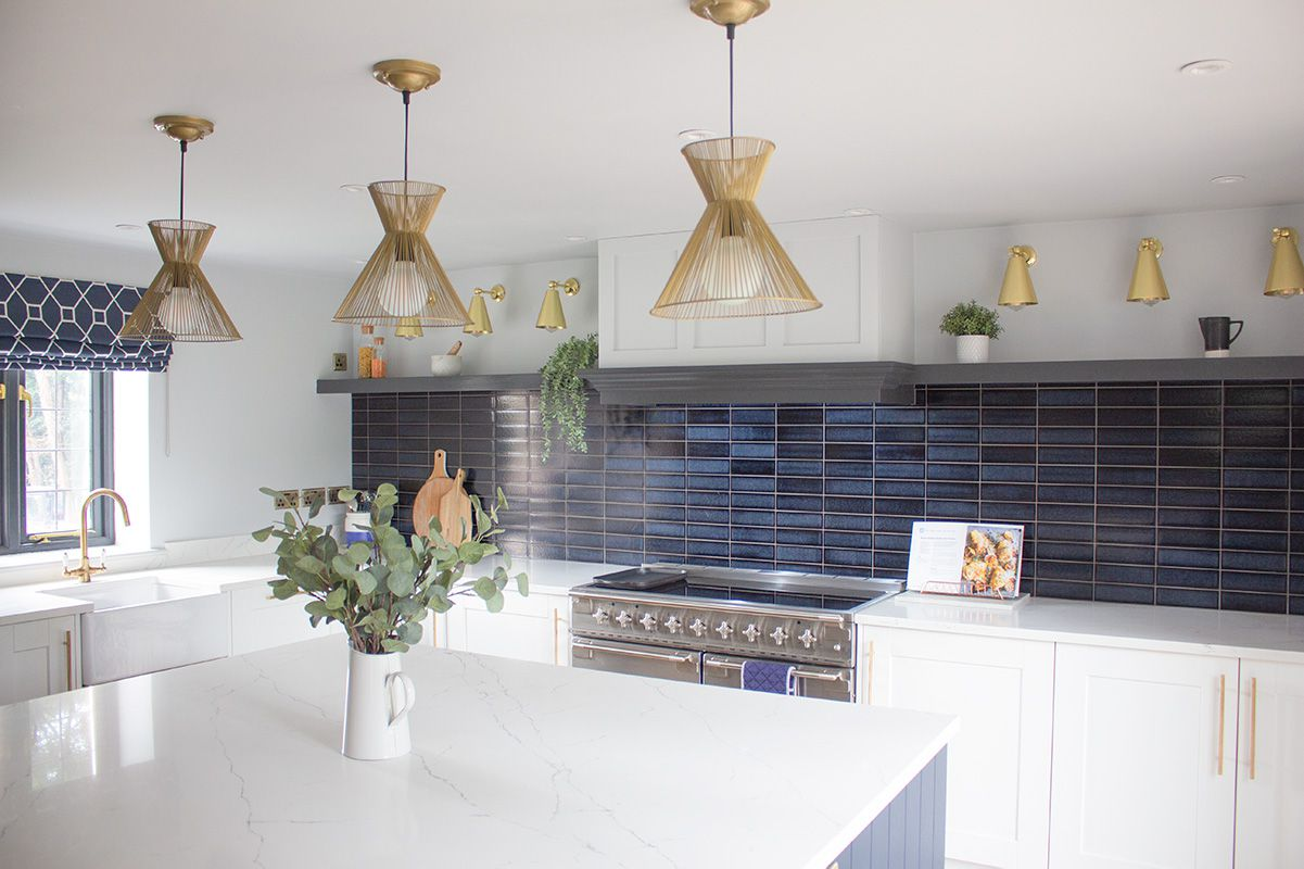 A view of the kitchen with the white shaker style units, marble worktops and brass lighting.