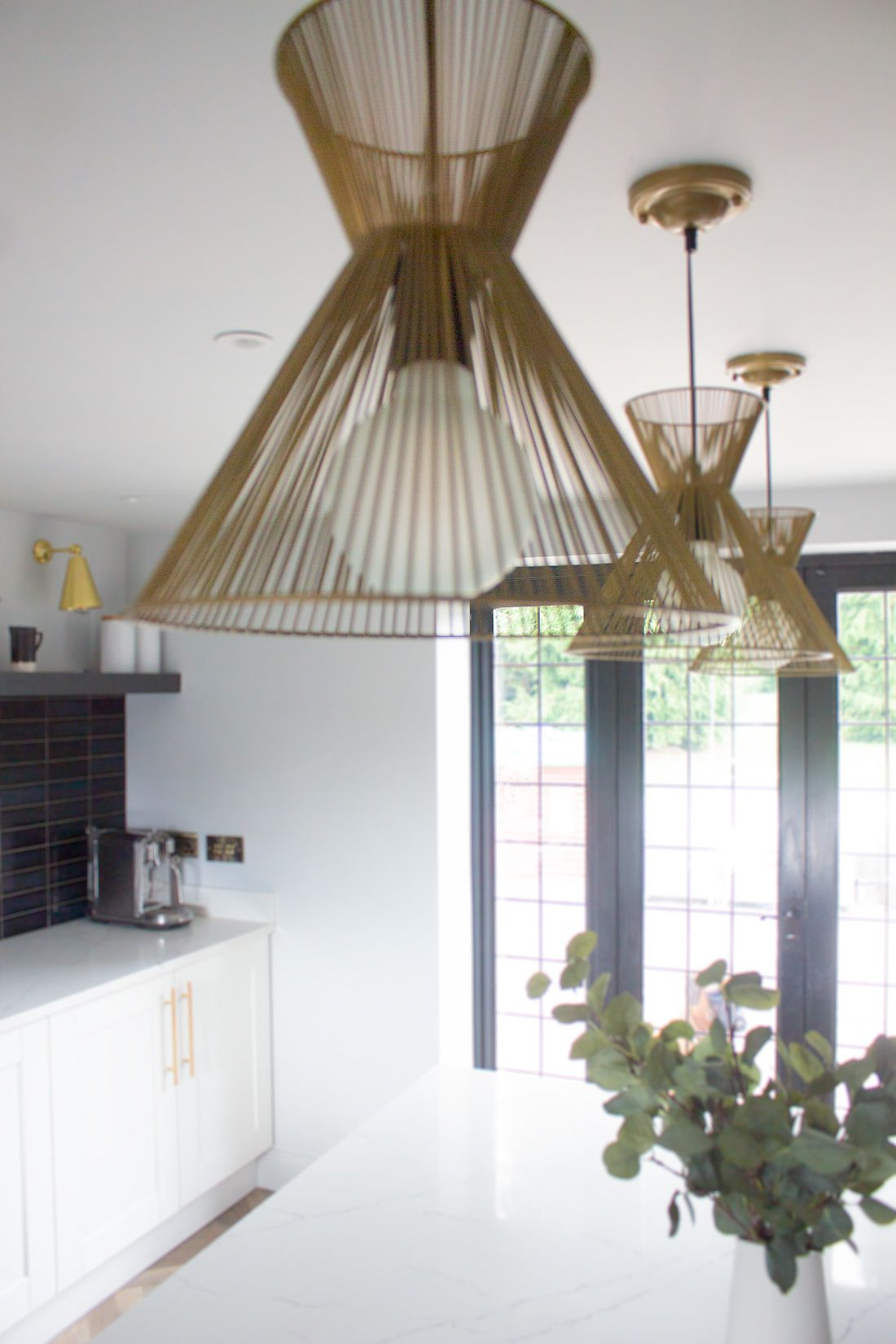 A photo showing the brass lights over the island, with the newly painted black French doors in the background.