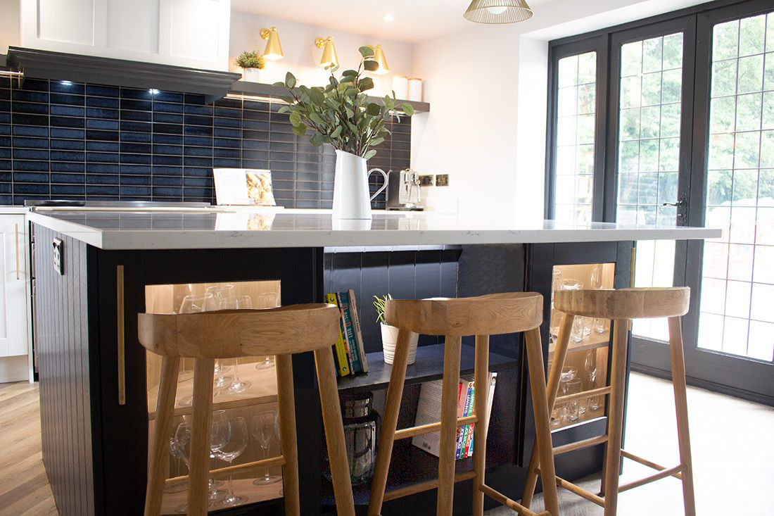 A photo of the navy kitchen island with the wooden bar stools underneath.