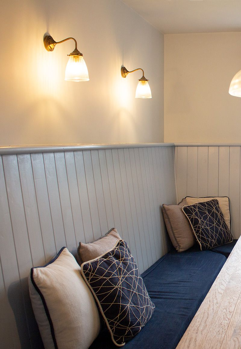 A close up of the wall lights above the seating area, switched on and giving off a soft glow.