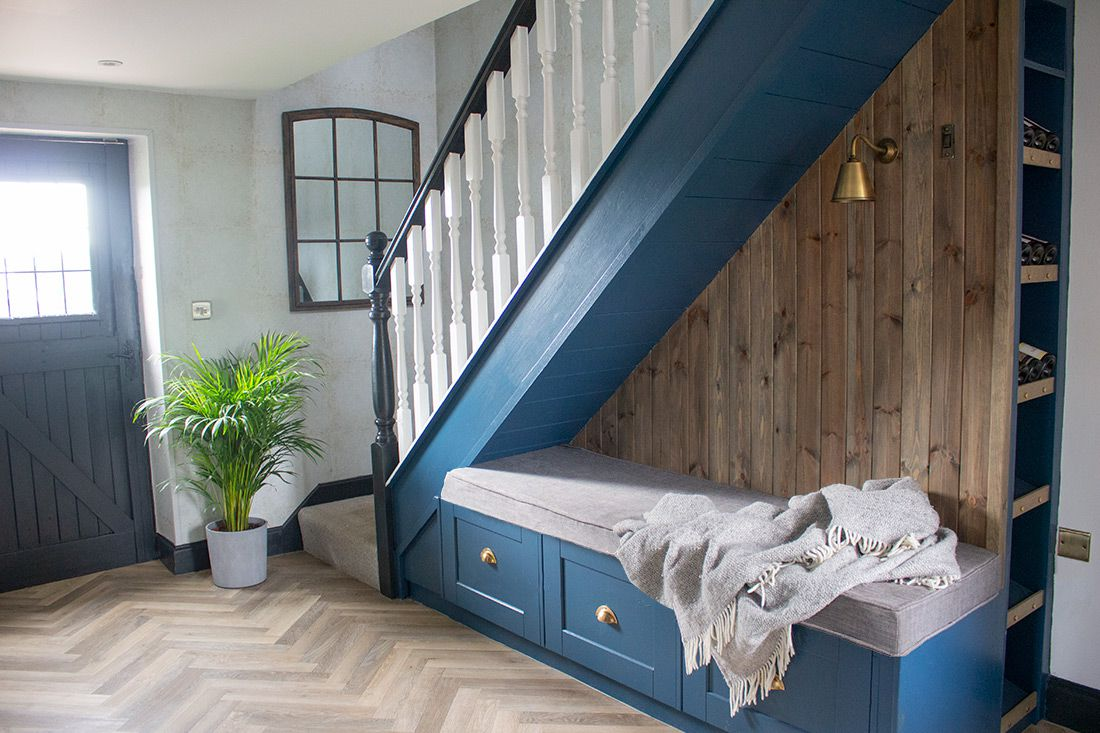 A photo of the hallway, with dark blue painted under stairs seating and storage.