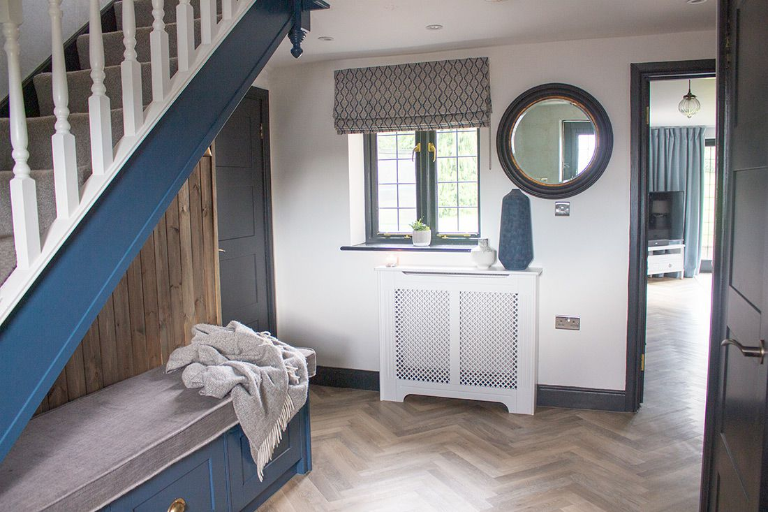 A view of the hallway showing the wooden radiator and a bespoke roman blind.