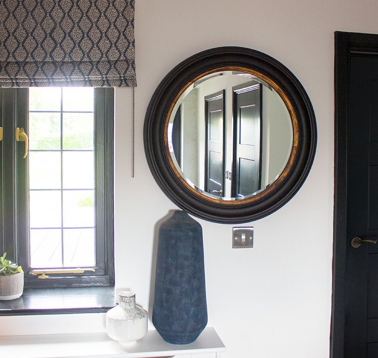A close up of the black round mirror, with a reflection of the black doors in the hallway.