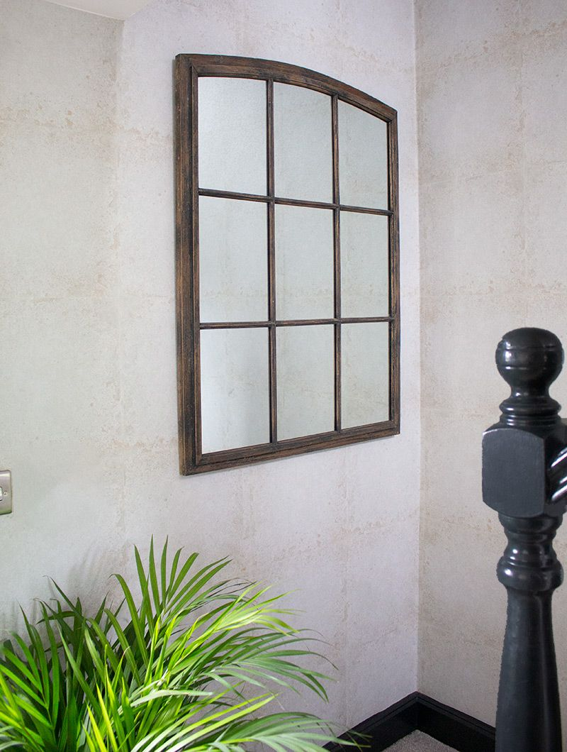 A close up of the industrial style window mirror at the bottom of the stairs.
