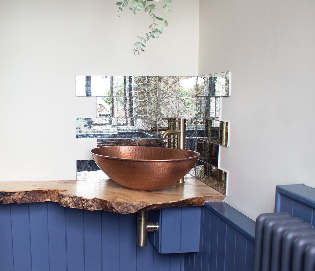 The new sink area with wooden shelf, countertop sink and foxed mirror tiles behind.