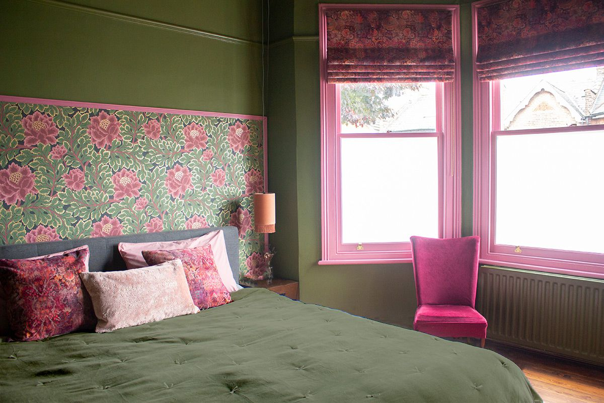 A photo looking across the bed to the pink framed windows.