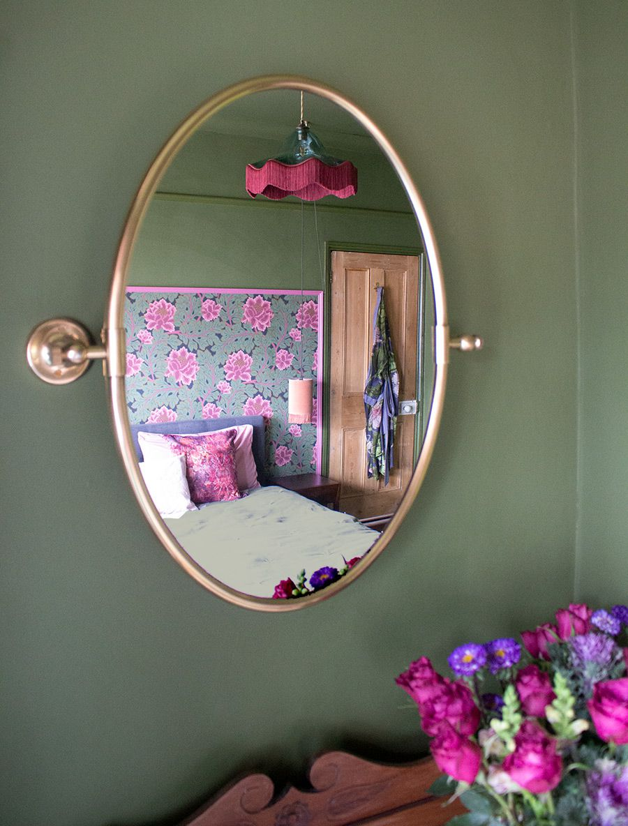 A view of the room looking through an oval brass mirror.