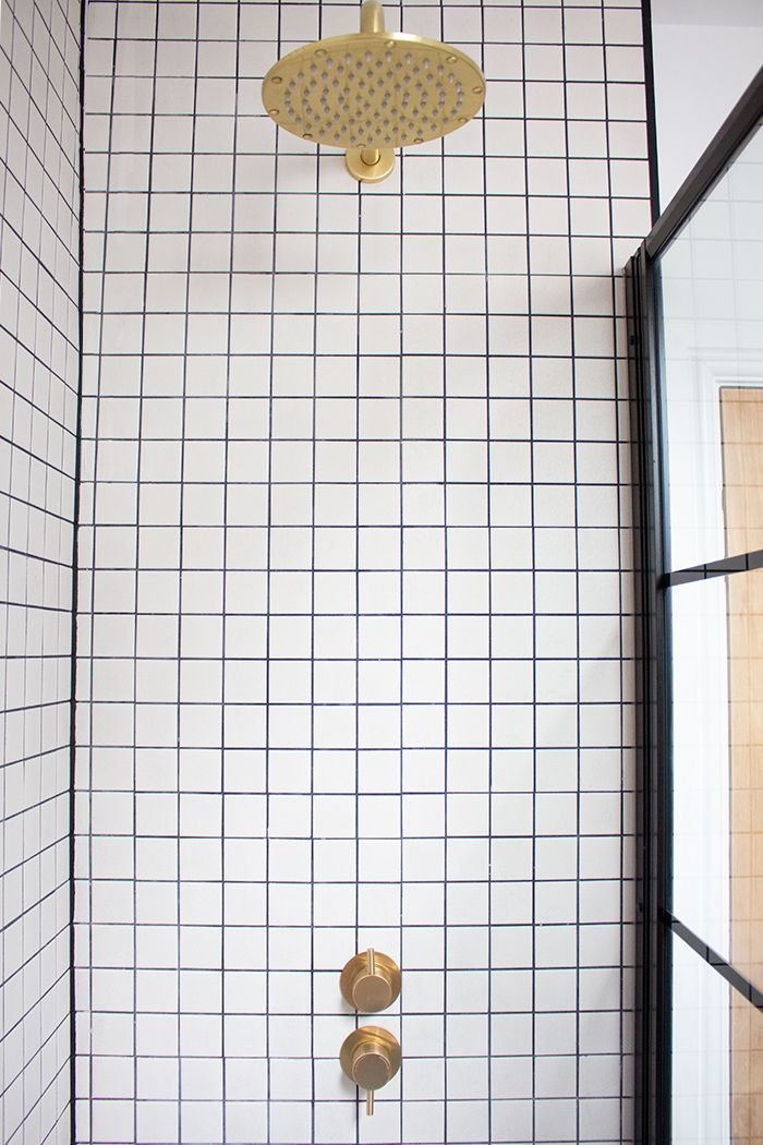A photo of the new brass shower head and valve with the square grid tiles around them.