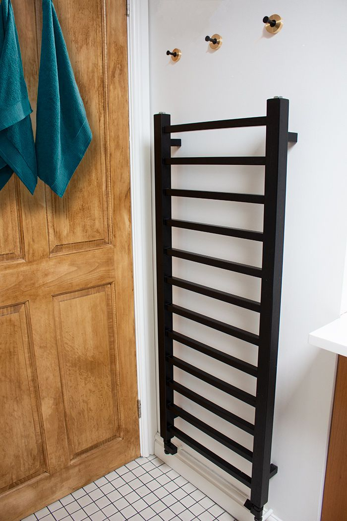 A photo of the new black radiator on the wall, with hooks above it..