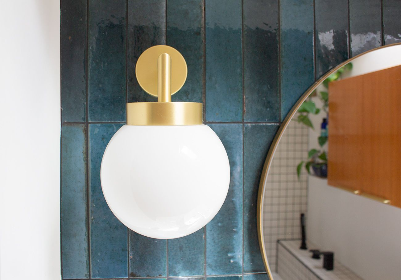 A close up photo of one of the globe lights by the sink.