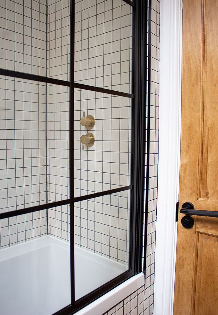 A photo of the Crittall style shower screen, where you can see the brass shower valve through it.