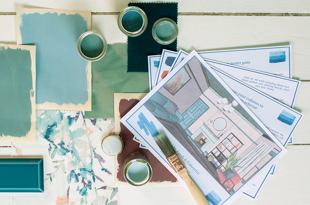 A photo of an example room colour scheme with some open paint pots, a paint brush and some fabrics artfully placed around it.