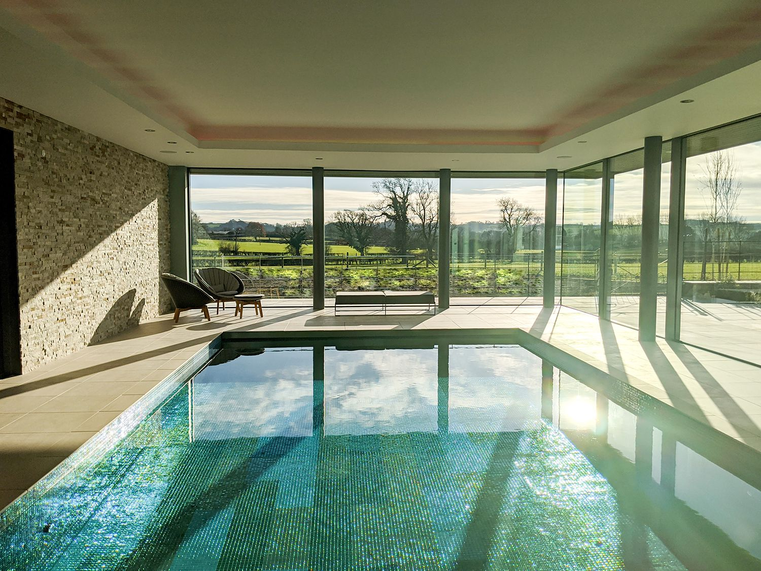 A photo looking down the length of the pool to the glazing and fields beyond.