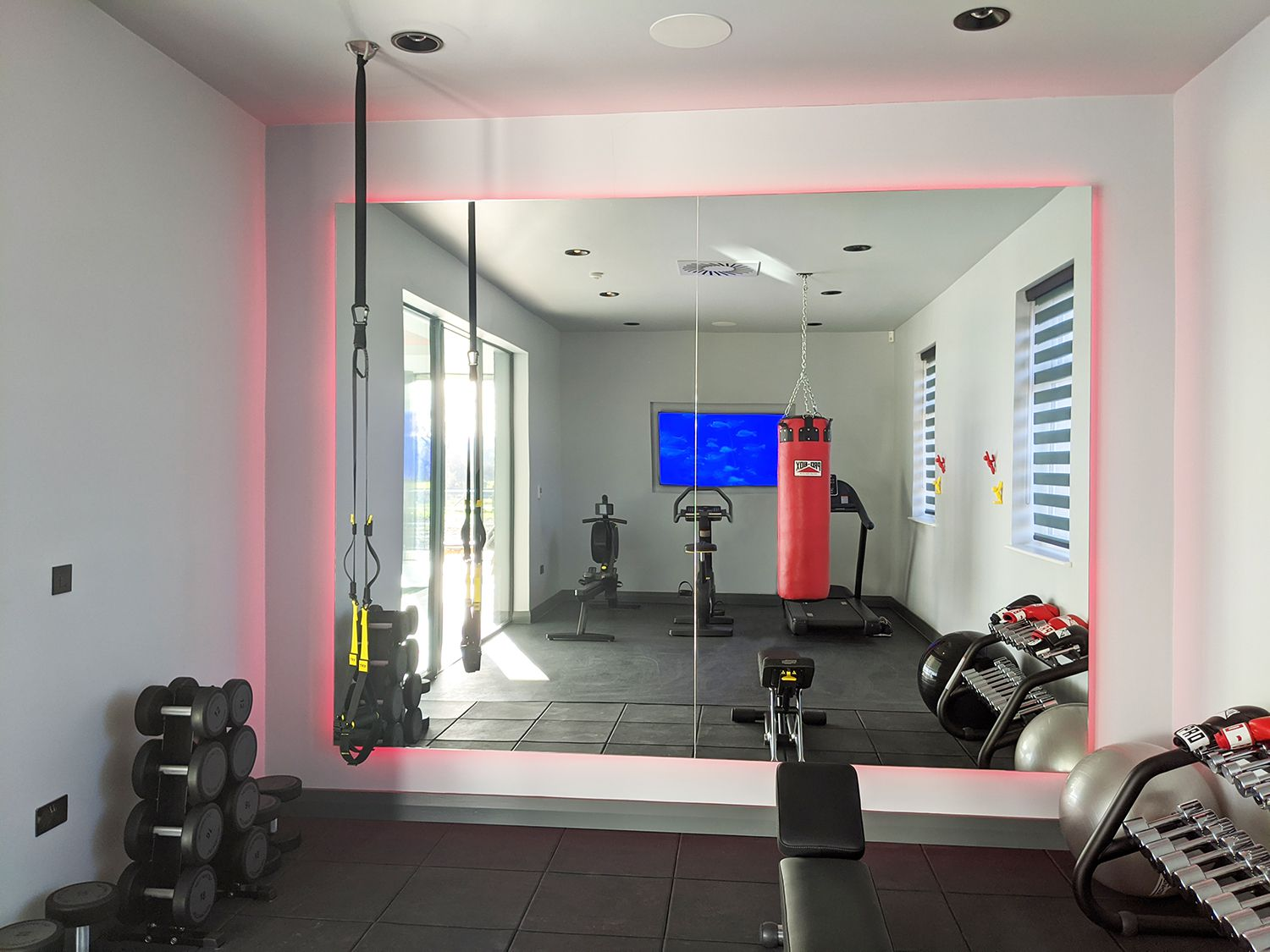 A photo of the gym area, with LED lights around a huge mirror.