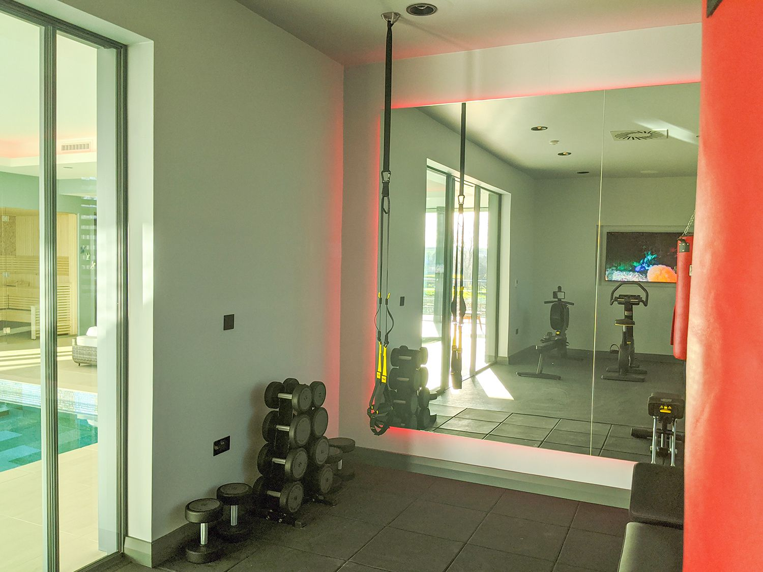 A photo of the gym, showing the glazed doors to the pool beyond.